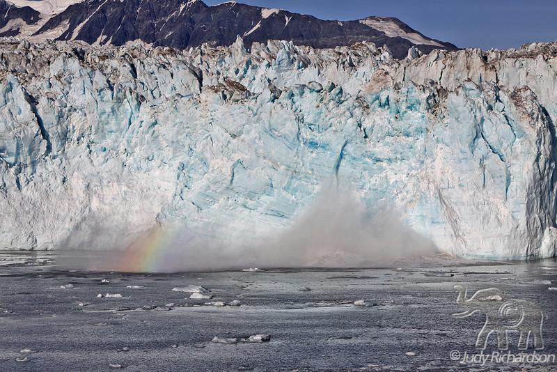 Rainbow in calving mist of Hubbard Glacier