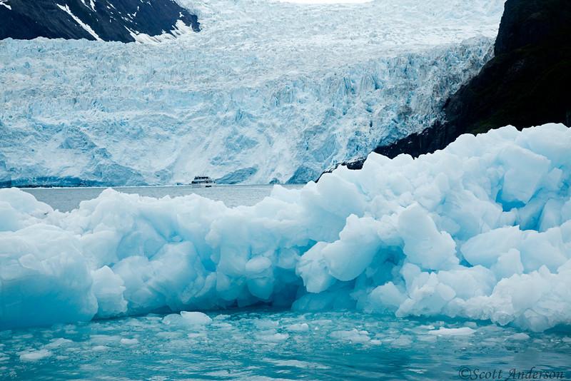 A tour boat is dwarfed by the glacier.