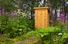 An outhouse in the bush with flowers near Ninilichik, Alaska, USA, America.