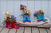 A display of colorful fishing boots with decorative flowers on the boardwalk on the Kenai peninsula in Homer, Alaska, USA, America.