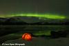 View of the Aurora Borealis (Northern Lights) dancing above the Chugach Mountains and a backpacking tent along Turnagain Arm, Kenai Peninsula, Alaska<br /> <br /> March 17, 2013