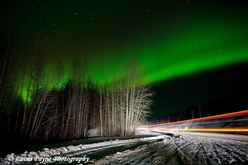 The aurora borealis over the Parks Highway in Alaska. <br /> (The streak of lights on the right was from a passing semi during my exposure. It helped to light up the trees and the surrounding area.)<br /> October 28, 2008