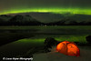 View of the Aurora Borealis (Northern Lights) dancing above the Chugach Mountains and a backpacking tent along Turnagain Arm, Kenai Peninsula, Alaska<br /> <br /> March 17, 2013