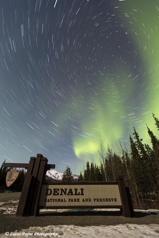 The Aurora Borealis (Northern Lights) and stars circling above the sign marking the entrance to Denali National Park and Preserve, Interior Alaska.<br /> <br /> April 12, 2014