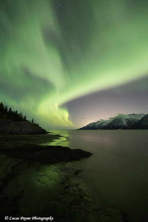 View of the Aurora Borealis (Northern Lights) dancing above the Chugach Mountains and Turnagain Arm, Kenai Peninsula, Southcentral, Alaska.<br /> <br /> November 04, 2015