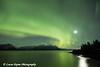 View of the Aurora Borealis (Northern Lights) and the moon above the Chugach Mountains and Turnagain Arm, Kenai Peninsula, Southcentral, Alaska.<br /> <br /> November 04, 2015