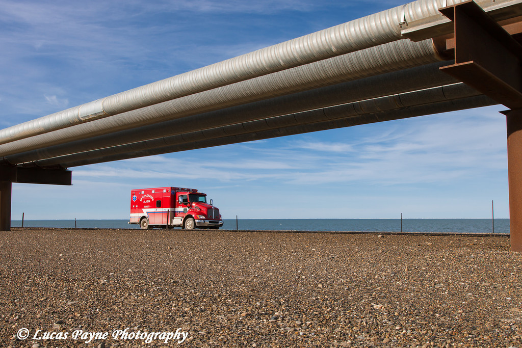 An ambulance driving on the Endicott Island causeway with oil pipelines, Prudhoe Bay Oil field, North Slope, Arctic Alaska<br /> <br /> July 28, 2012
