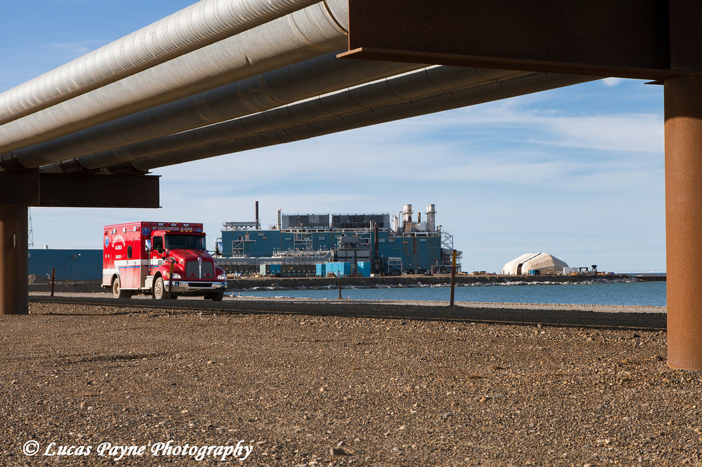 An ambulance driving on the Endicott Island causeway with the Endicott oil facility in the background, Prudhoe Bay Oil field, North Slope, Arctic Alaska<br /> <br /> July 28, 2012