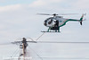 A helicopter crew using a long probe to clean the insulators on a high voltage tower at the Milne Point Unit Oilfield, North Slope, Arctic Alaska.<br /> <br /> October 12, 2013
