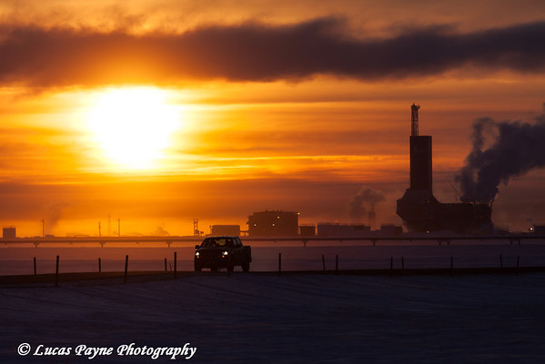 Pickup truck driving down the road with Parker Drilling Rig 273 on Drill Site 2 at Sunrise, Prudhoe Bay Oilfield, North Slope, Arctic Alaska<br /> <br /> January 30, 2013