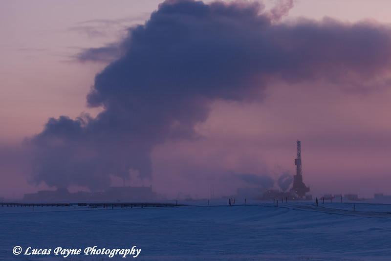 Exhaust fumes from Flow Station 3 fill the sky and a Doyon Drilling Rig at dusk in the Prudhoe Bay Oil Field, North Slope, Arctic Alaska<br /> <br /> February 07, 2013