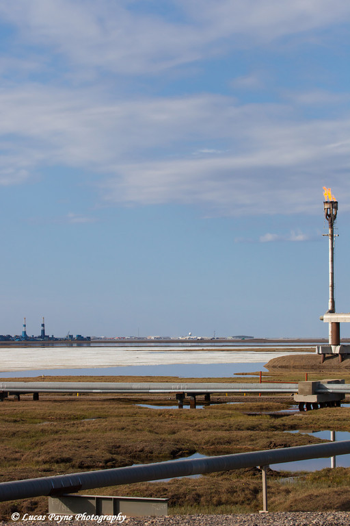 Flare tower at Flow Station 1 (FS1) with oil rigs and Deadhorse in the background, Prudhoe Bay Oil Field, North Slope, Arctic Alaska<br /> <br /> June 23, 2012