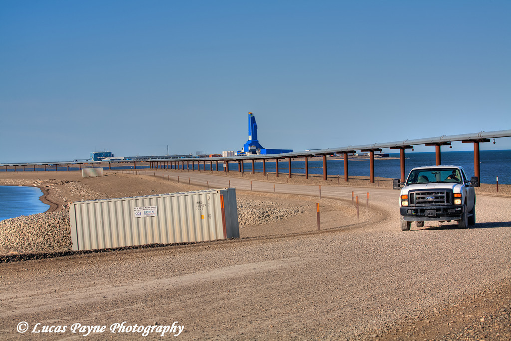 Pickup truck driving on gravel road in Prudhoe Bay Oilfield with the Liberty Oil Rig and pipeline in the background, Arctic Alaska<br /> July 28, 2011