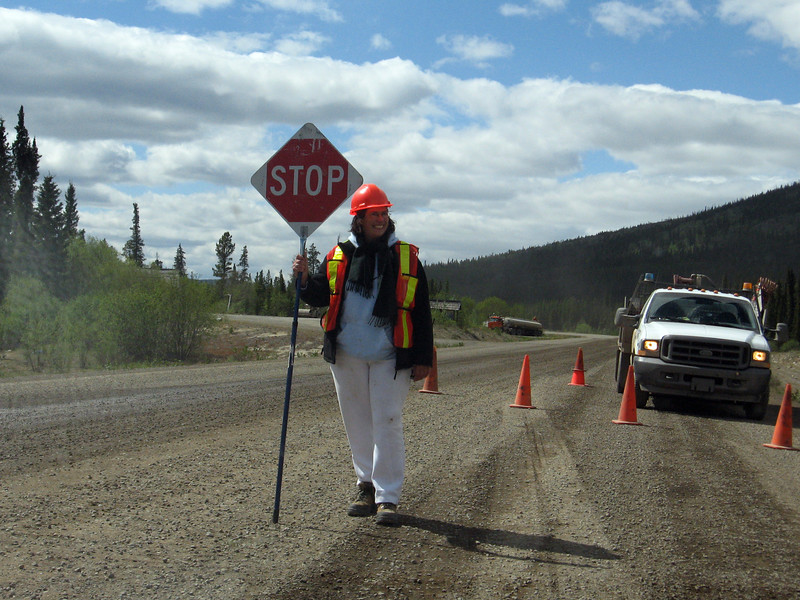 Traffic control at a construction site on the Alaska Highway near Johnson's Crossing. Why is this person wearing white working on a unpaved road?