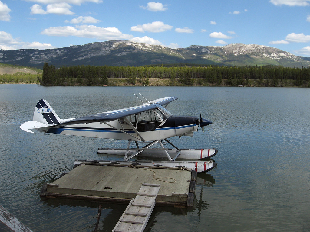 Float plane on the Yukon River, Grey Mountain in the background.