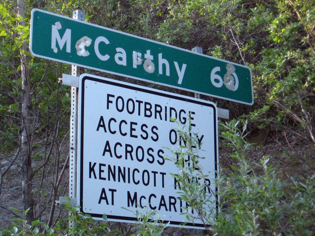 """Gunshot graffite"" adorns the sign at the beginning of the McCarthy Road."