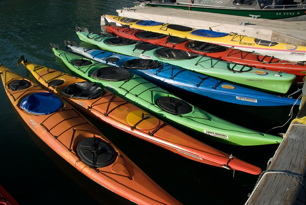 Colorful array sea kayaks at dock.