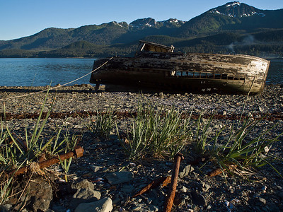An old boat with old bolts in foreground sits aground just off the road to Thane, South of Juneau. A rope keeps it from becoming a navigational hazard at high tide. July 9th, 2010.