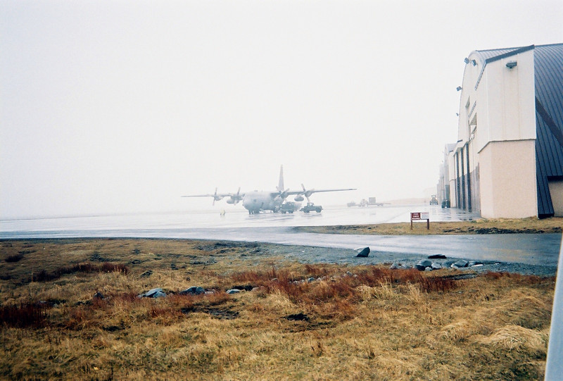 Air Force C-130 refueling near the hangars on a foggy day.