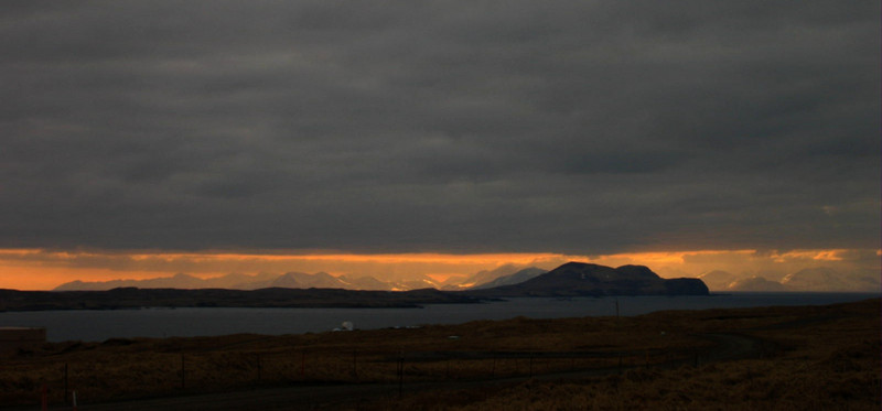 The mountains in the far background, where the sun is shining, is Attu Island.  Attu is the last island in the Aleutian chain.