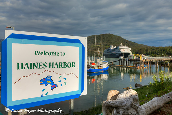 Welcome to Haines Harbor sign and Holland America Cruise Ship Oosterdam docked at the Port of Haines, Southeast Alaska.<br /> <br /> July 02, 2014