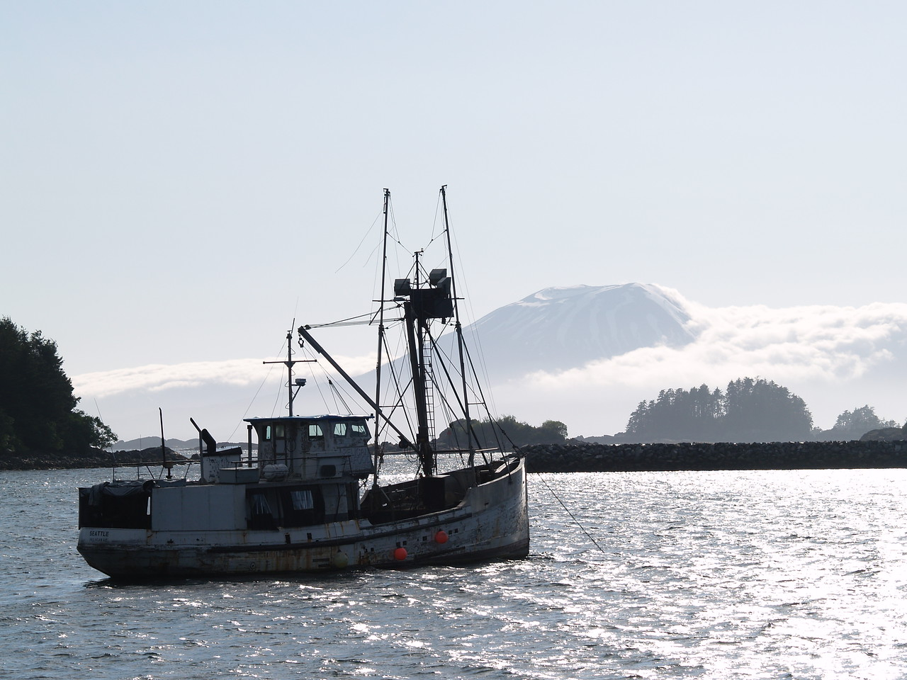 """The Alaska Arts Council was holding their annual meeting in Sitka while I was there. They sponsored an """"arts cruise"""" hosted by Alaska's writer laureate John Straley. He writes murder mysteries and lives in Sitka. I've read and own some of his books. We came across this old trawler anchored with Mt. Edgecumbe in the background. It was a beautiful, clear late June day."""