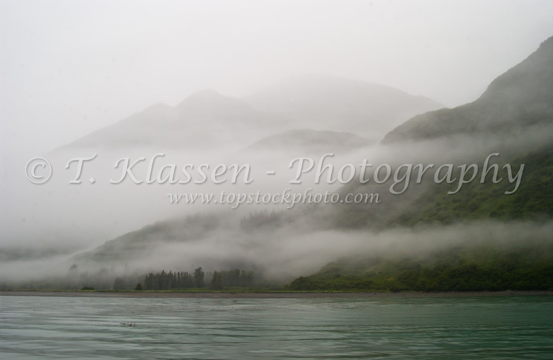 Layers of mist and low hanging clouds cover the mountains at Valdez harbor, Alaska, USA, America.