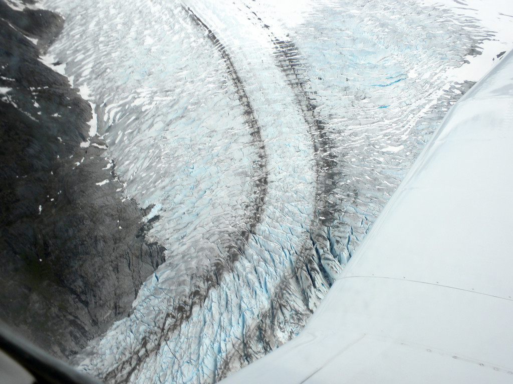 Flying over the glaciers. The blue color is the result of the compressed ice, the brownish color by the rocks dragged down the mountainside with the ice.