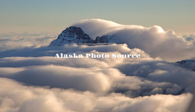 Alaska. In this aerial view, windflow has clouds are streaming over peaks in the Alaska Range southeast of Mt. Foraker, Denali Natl. Park.