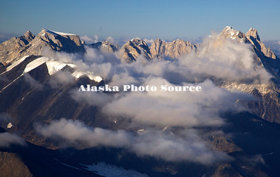 Alaska. In this aerial view, clouds highlight the drama of the Cathedral Spires and Gurney Peak (left) in the Kichatna Mountains, Denali National Park & Preserve.