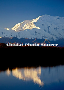 Mt. McKinley is basked in warm, morning light while mirrored in Reflection Pond, Denali National Park & Preserve.