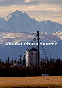 Alaska. Dramatic scenic view of Delta Junction barley fields and grain silo with mountains of the Alaska Range in the Background.