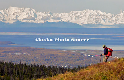 Recreational hiker on the Anchorage hillside in Chugach State Park, with south Anchorage, Cook Inlet and the Alaska Mountain Range in the background.