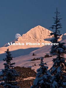 Alaska. Alpine glow on the mountains at Turnagain Pass, with the moon peaking over.