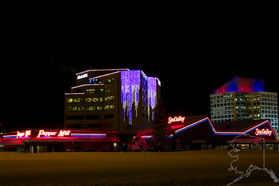 Anchorage on a winter night. Alaska USA is a bank and The Sea Galley is a sea food restaurant.