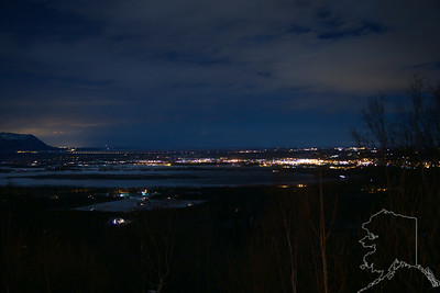 This is Palmer Alaska at night. It was about 9:30 pm when I took this shot. Look to the left and you can see the glow of Anchorage. You can also see the planes coming in to land at the Anchorage air port. The yellow lights that are in a lin and snake there way around the mountain is the main road to Anchorage.