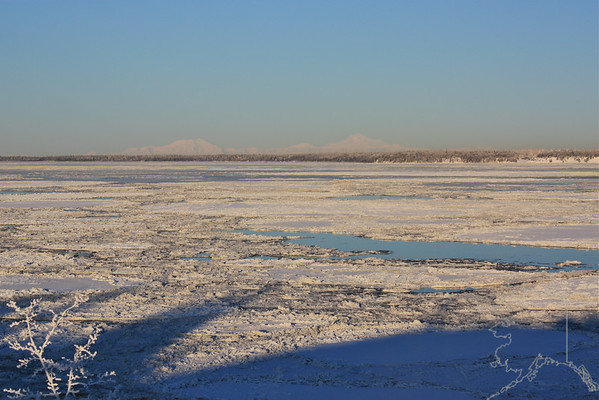 This is looking north from Anchorage at the end of the airport over looking Cook Inlet. You can see Mt. Mckinley (the peak on the right) and it is about 237 road miles away. Mt. Mckinley stands at 20,320 feet high and is growing a few inches every year.