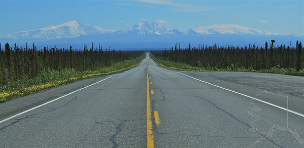 Glenn Highway headed  toward Wrangell St. Elias. Mount Wrangell itself, a massive shield-shaped volcano and namesake of the range, still signals its active presence with steam plumes, while nearby, Mounts Sanford, Drum, and Blackburn lie dormant.