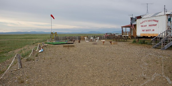 The last checkpoint before Nome, just 22 miles away. Here the mushers are on the coast of the Bering Sea and travel on the beach most of the way to Nome. The elevation of Port Safety is 0 feet. The Safety Sound roadhouse still opens in summer to offer travelers shelter from the rain or a cool beverage to wash down the dust. It's closed the rest of the year except for several weeks in March, when it serves as the final checkpoint for the Iditarod Trail Sled Dog Race. The Safety Bridge is a good vantage point to watch changing tides and the movement of large and small fish and their predators. Scan for the bobbing heads of seals attracted by the summer fish runs. They are most likely young spotted seals, which remain in coastal waters for the summer rather than follow the ice edge north. Salmon enter through the channel during certain light, tide, and wind conditions. Birds feed on escaping salmon smolt or arriving capelin and herring. They include large numbers of eiders, scoters, gulls, kittiwakes, and terns. Look for herring eggs near the lagoon entrance among the mounds of eel grass that wash up along the beach in spring. On the lagoon side, shorebirds and gulls collect on the extensive mud flats at low tide. Take time to search for rare species that mix with the large numbers of common species.