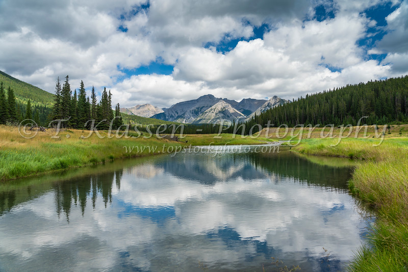 Scenic mountain reflections with a meadow near Lake Minnewanka, Banff National Park, Alberta, Canada.