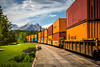 A freight train and mountain scenery at the Lake Louise train station in Banff National Park, Alberta, Canada.