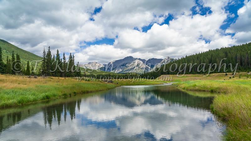 Scenic mountain reflections with a meadow near Lake Minnewanka, Banff National Park, Alberta, Canada.