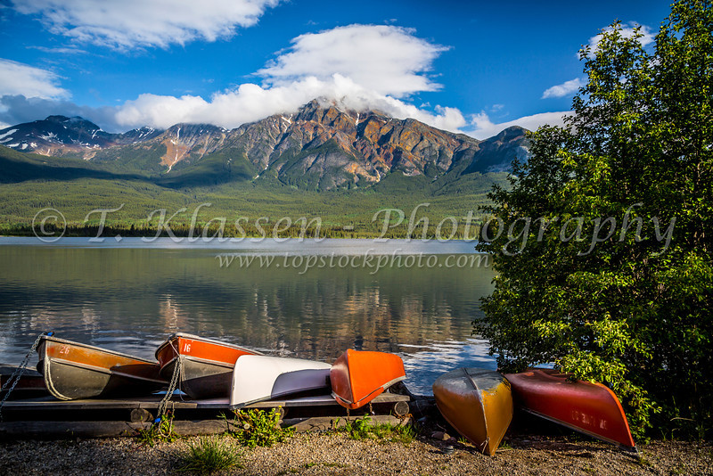 Colorful canoes on Pyramid Lake with reflections of Pyramid Mountain in Jasper National Park, Alberta, Canada.