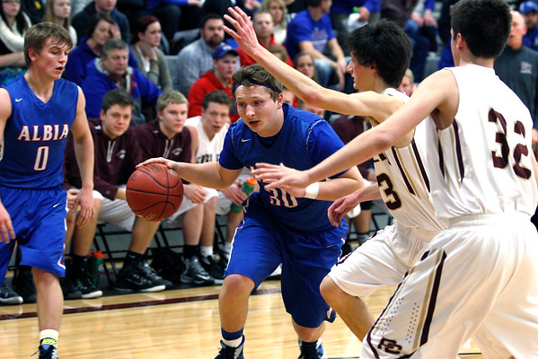 RACHEL LEATHE/ THE COURIER<br /> <br /> 022316 Alba High School senior Bret Freshwater attempts to drive to the net and is deflected by Pella Christian High School's defense in Tuesday evening's boys varsity basketball game in the Oskaloosa High School Gymnasium.