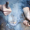 Local Farrier shoeing a horse, the red hot metal makes the smoke rise as he measures up the horseshoe for fitting