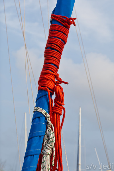 Sheets around a furled genoa on a sailboat.