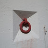 Red steel ring in wall with shadows.