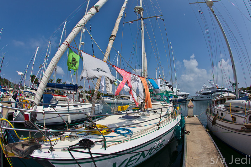 Laundry day on a sail boat. - Colorful laundry drying in the breeze on the deck of a sail boat in the tropics.