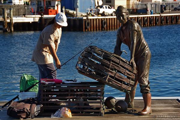 Una joven pescadora junto al monumento dedicado a los pescadores.<br /> <br /> A young fisherwoman next to the monument to the fishermen.