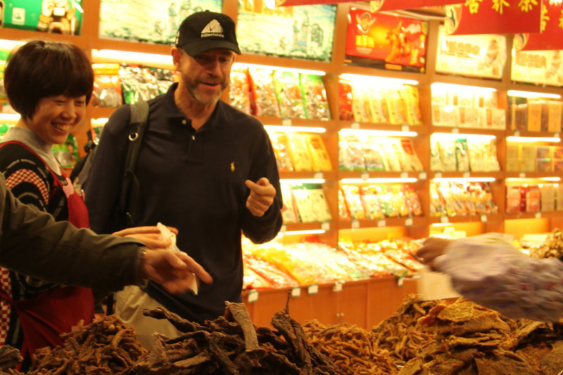 She, and ~3 others to the right, were encouraging me to taste each type of their jerky. Dujiangyan old town.
